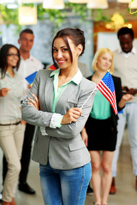Smiling businesswoman holding flag of USA in front of colleagues