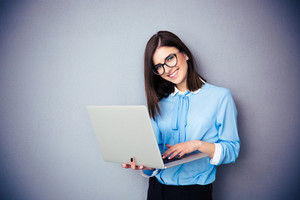 Smiling businesswoman standing and using laptop over gray background. Wearing in blue shirt and glasses. Looking at camera
