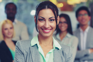 Smiling businesswoman standing in front her colleagues