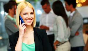 Smiling businesswoman talking on the smartphone in front of colleagues