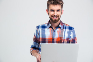 Smiling casual man using laptop