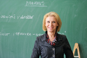 Smiling caucasian teacher on a chalkboard