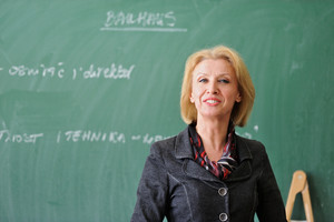 Smiling caucasian teacher standing in front of a blackboard