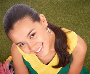 Smiling Cheerleader Sitting On Grass