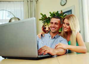 Smiling couple using laptop together at home