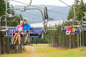 Smiling couples using chair lift in scenic landscape