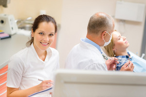 Smiling dental nurse prepare patient documentation stomatology clinic