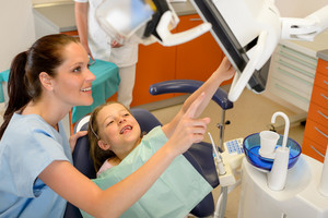 Smiling dentist and child pointing at the screen stomatology office