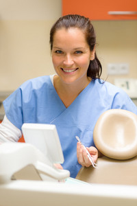 Smiling dentist woman prepare dental tools at modern surgery office
