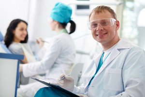 Smiling doctor in protective eyewear looking at camera