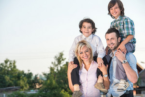 Smiling family with two kids outdoors