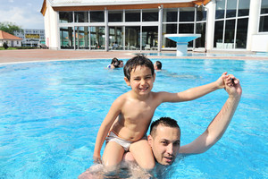 Smiling father and son leaning in the water pool