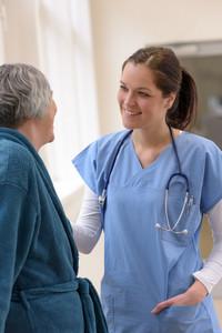 Smiling female doctor taking care of senior patient in hospital corridor