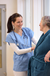 Smiling female nurse helping senior patient in hospital corridor