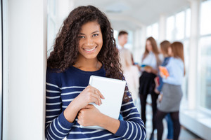 Smiling female student standing in university hall