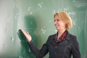 Smiling female teacher pointing to a blackboard