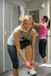 Smiling fit woman tying shoelaces at gym's locker room