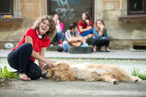 Smiling girl petting a dog lying on the street