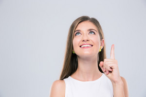Smiling girl pointing finger up at copyspace