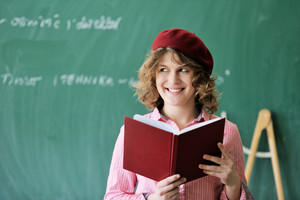 Smiling girl with a red cap in front of a blackboard