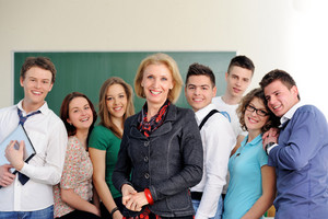 Smiling group of students posing with their professor on a chalkboard