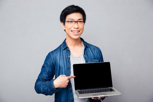 Smiling handsome asian man showing on laptop screen