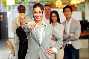 Smiling handsome businesswoman with team in office pointing finger at you