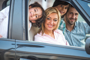 Smiling happy family sitting in automobile