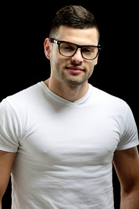 Smiling male model with glasses standing in front of dark background