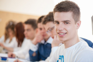 Smiling male student sitting in a schoolroom