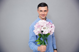 Smiling man holding flowers