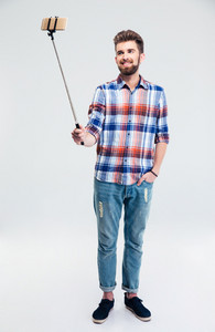 Smiling man making selfie photo with stick