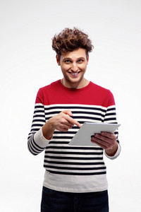 Smiling man using tablet computer over gray background