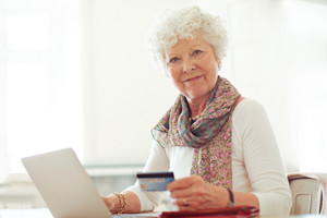 Smiling mature lady holding a credit card in front of her laptop