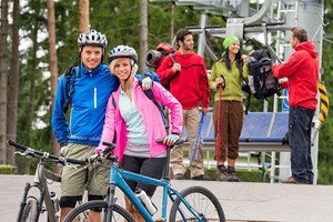 Smiling mountain bikes couple and hikers waiting after chair lift trip