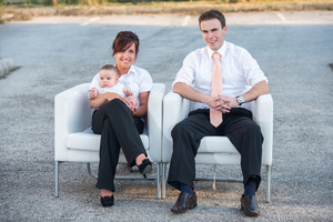 Smiling parents sitting with baby in armchairs outdoors