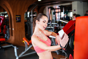 Smiling playful young sportswoman taking selfie using mobile phone in gym