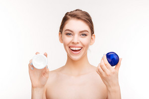 Smiling pretty woman holding moisturizing facial cream isolated on a white background