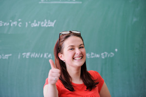 Smiling schoolgirl in front of blackboard showing thumb up