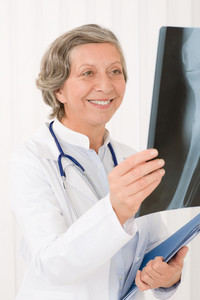 Smiling senior doctor female looking at x-ray with stethoscope portrait