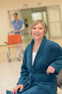 Smiling senior female patient waiting in  hospital for nurse with wheelchair
