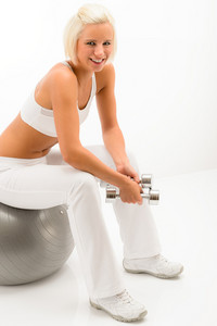 Smiling sport woman sitting on fitness ball hold dumbbells