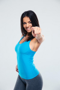 Smiling sports woman pointing finger at camera over gray background. Looking at camera