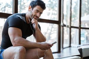 Smiling sportsman wearing black t-shirt listening to music