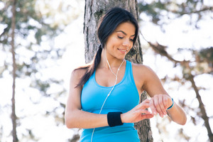 Smiling sporty woman using smart watch