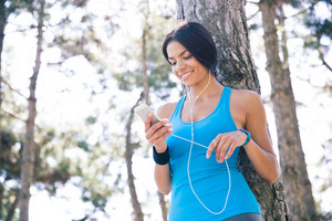 Smiling sporty woman using smartphone outdoors
