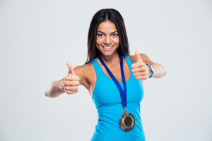 Smiling sporty woman with medal showing thumb up sign