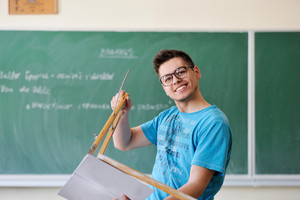Smiling student holding a compass and a book in front of a chalkboard