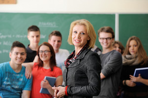 Smiling teacher standing in a classroom with students behind her