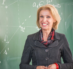 Smiling teacher standing in a classroom